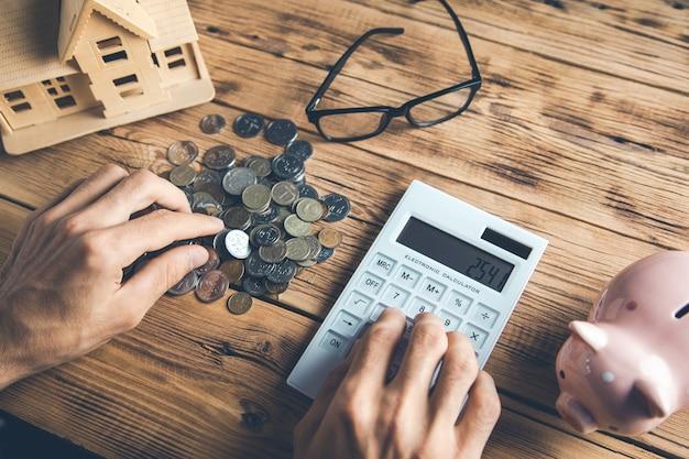 Biznesmen za pomocą kalkulatora model domu i stos monet na biurku