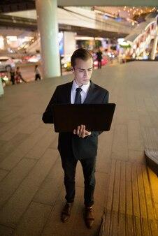 Biznesmen za pomocą laptopa na zewnątrz w nocy w mieście