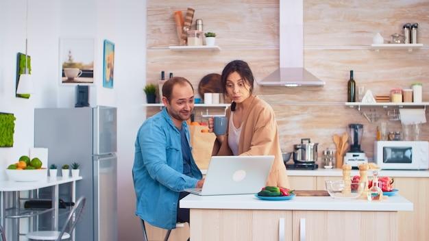 Biznesmen za pomocą laptopa w kuchni i żona pije kawę. mąż i żona gotowanie żywności przepis. szczęśliwy zdrowy styl życia razem. rodzina szukająca posiłku online. zdrowa świeża sałatka
