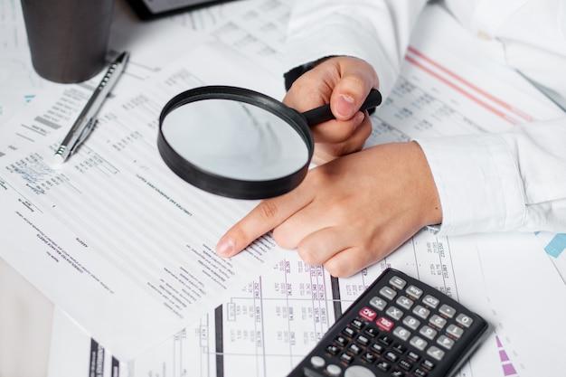 Biznesmen za pomocą lupy do przeglądu annua bilansu