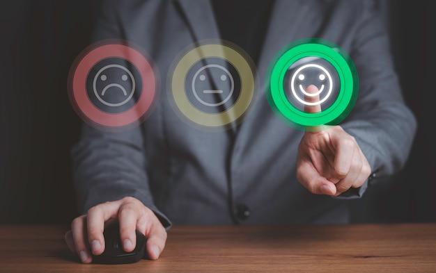 Biznesmen za pomocą myszy komputerowej i naciskając przycisk uśmiechu, aby uzyskać najlepszą ocenę, pojęcie satysfakcji klienta.