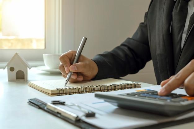 Biznesmen za pomocą pióra do robienia notatek w tym kalkulator i sprawozdania finansowe na stole.