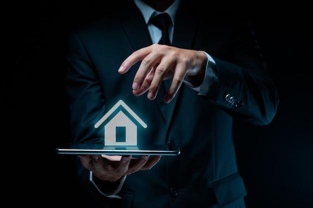 Biznesmen za pomocą planowania tabletu z efektem hologramu ikony domu