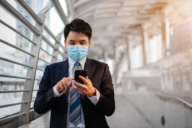 Biznesmen za pomocą smartfona i nosząc maskę medyczną podczas pandemii koronawirusa w mieście