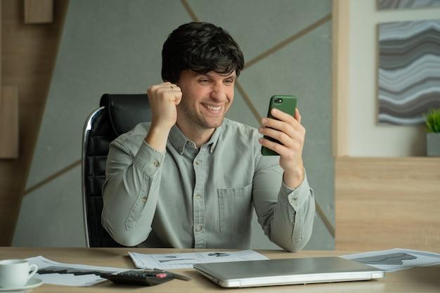 Biznesmen za pomocą smartfona siedzi w biurze, mając dobre wieści na telefonie
