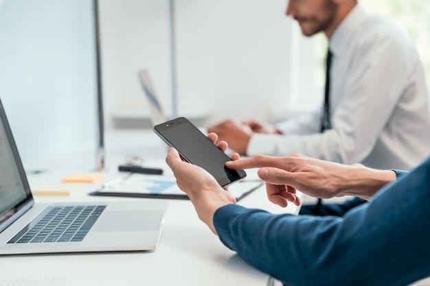 Biznesmen za pomocą swojego smartfona w biurze