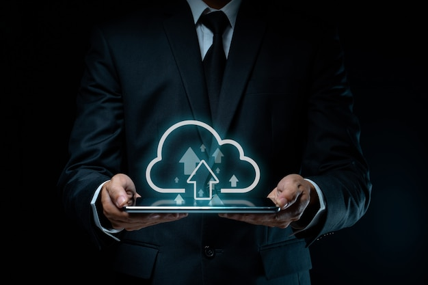 Biznesmen za pomocą tabletu do przesyłania z efektem hologramu ikony chmury