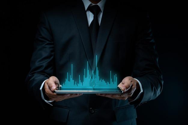 Biznesmen za pomocą tabletu planowania marketingu cyfrowego z efektem hologramu wykresu