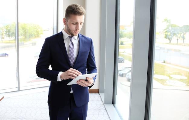 Biznesmen za pomocą tabletu w biurze.