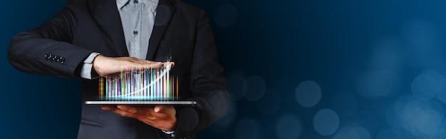 Biznesmen za pomocą tabletu z wykresem handlu. wykres analizy marketingu giełdowego. informacje statystyki wykres zysk. koncepcja inwestycji i marketingu.
