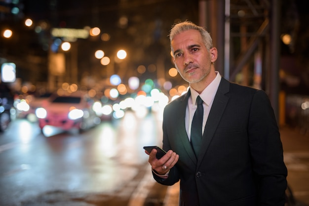 Biznesmen za pomocą telefonu komórkowego na zewnątrz w nocy podczas oczekiwania na taksówkę