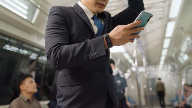 Biznesmen za pomocą telefonu komórkowego w pociągu publicznym. koncepcja dojazdów do pracy w stylu życia miejskiego miasta.