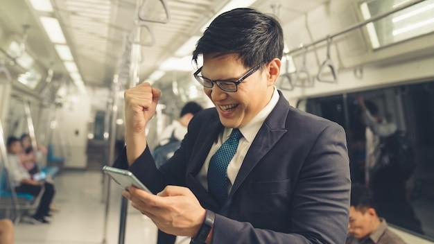 Biznesmen za pomocą telefonu komórkowego w pociągu publicznym