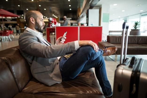 Biznesmen za pomocą telefonu komórkowego w poczekalni