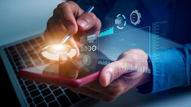 Biznesmen za pomocą zadań aktualizacji mobilnej z harmonogramem wykresów finansowych vr wirtualnym diagramem i planowaniem postępów kamieni milowych, wskazując piórem na górze telefonu komórkowego.