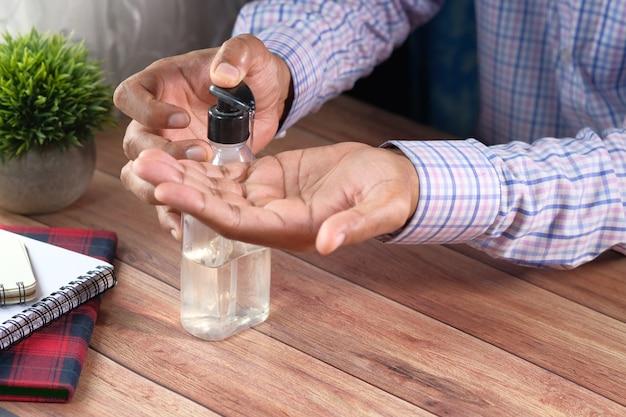 Biznesmen za pomocą żelu dezynfekującego na biurku.