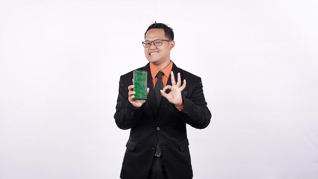 Biznesmen za pomocą zielonego telefonu komórkowego na białym tle z gestem ok