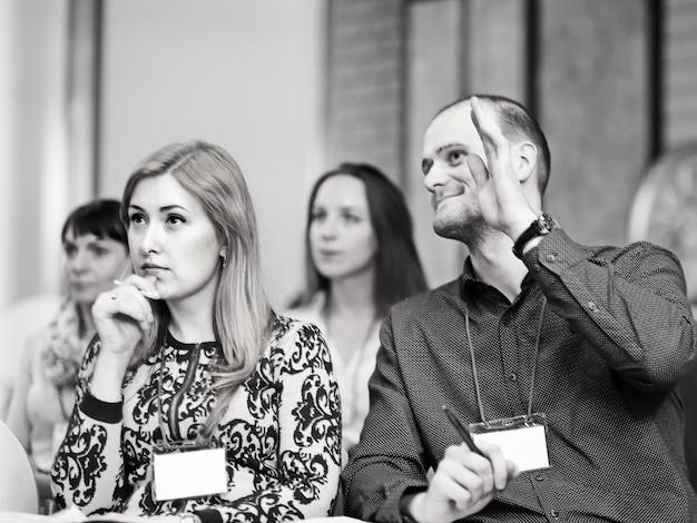 Biznesmen zadaje pytanie dotyczące prezentacji biznesowej. czarno-białe zdjęcie