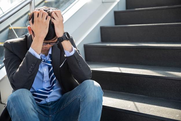 Biznesmen zagubiony w depresji płacz siedząc na schodach ulicy ziemi
