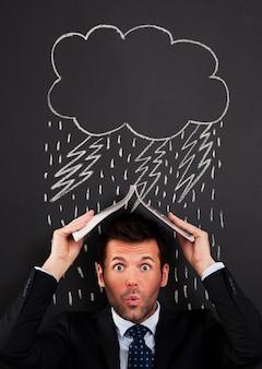 Biznesmen zakrywający głowę przed deszczem