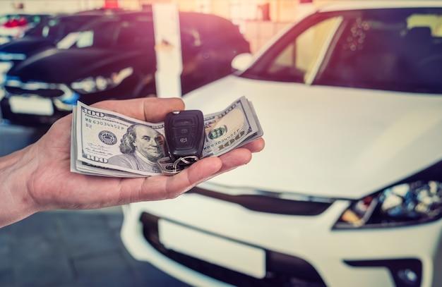 Biznesmen zakup nowego samochodu w salonie, dając pieniądze w dolarach i biorąc klucze od samochodu, koncepcja finansów
