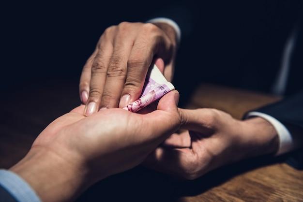 Biznesmen zamykając ofertę, dając pieniądze swojemu partnerowi w ręku