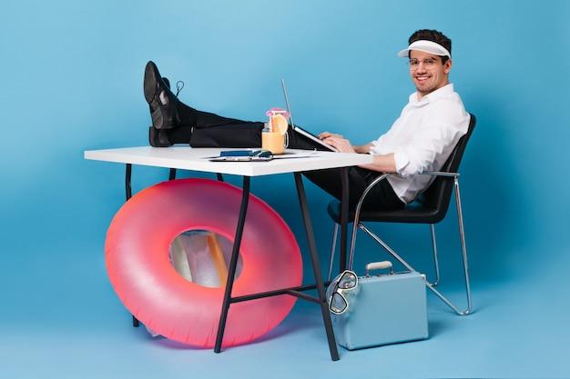 Biznesmen zapakował walizkę na wakacje i szczęśliwie pracuje. facet w ubraniach biurowych trzyma laptopa i patrzy w kamerę na niebieskiej przestrzeni z nadmuchiwanym kółkiem.