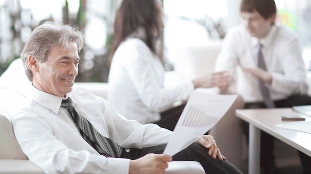 Biznesmen zastanawia się nad dokumentem siedzącym w nowoczesnym biurze.zdjęcie z miejscem na kopię