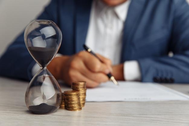 Biznesmen zatwierdza ważną umowę w biurze. stos monet i klepsydry na biurko z bliska. czas to pieniądz