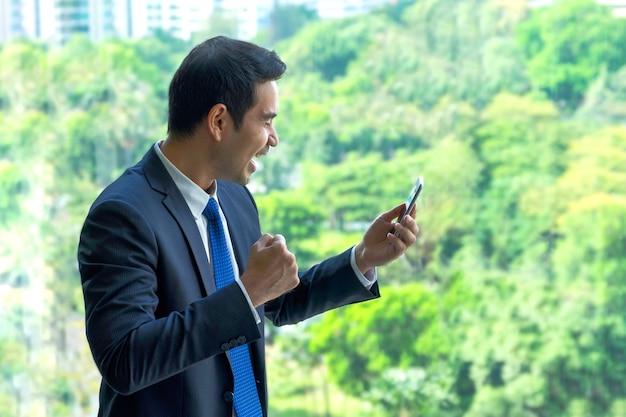 Biznesmen zbroi up i widzący dobre wieści na telefonie komórkowym przy biurem