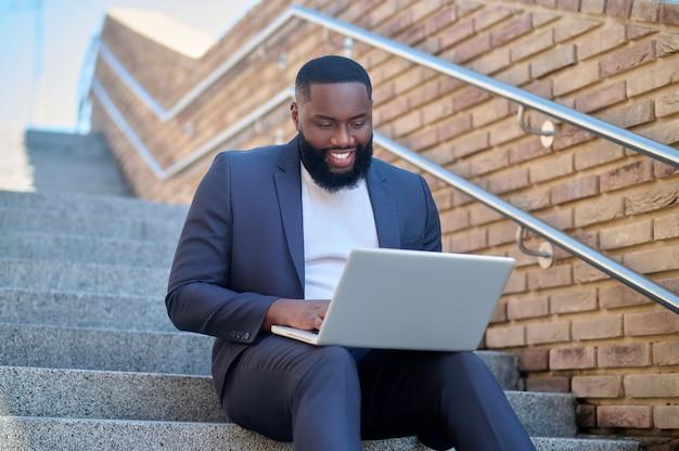 Biznesmen. zdjęcie ciemnoskórego mężczyzny w garniturze z laptopem