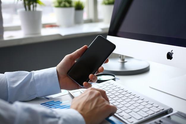 Biznesmen ze smartfonem i komputerem w biurze