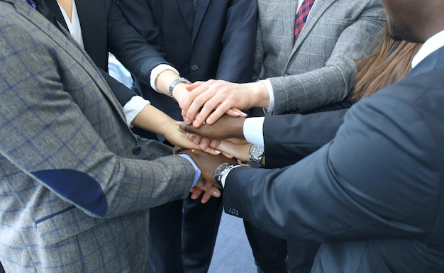 Biznesmen zespół w garniturze dotykając rękami razem. selektywne skupienie