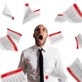Biznesmen zestresowany i przepracowany krzyczy w biurze z latającymi kartkami papieru