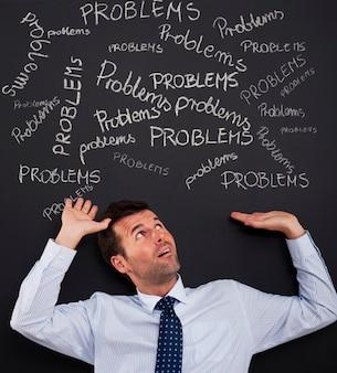 Biznesmen zginanie pod stosem problemów