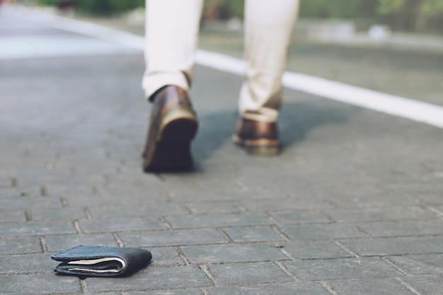 Biznesmen zgubił skórzany portfel z pieniędzmi na ulicy. zbliżenie portfela leżącego na chodniku podczas podróży do pracy. zostaw miejsce na pisanie wiadomości.