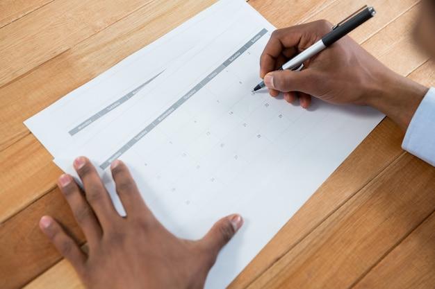 Biznesmen znakowanie piórem w kalendarzu