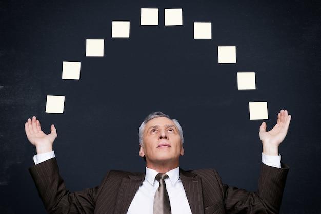Biznesmen żonglerka. pewny siebie starszy mężczyzna w formalnym stroju, żonglujący samoprzylepnymi notatkami, stojąc przy tablicy