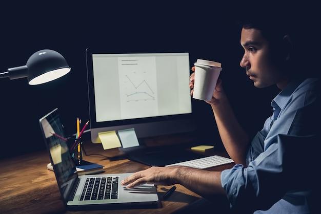 Biznesmen zostaje w godzinach nadliczbowych późno w nocy w biurze, koncentrując się na pracy z notebookiem
