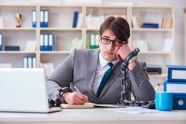 Biznesmen związany łańcuchami do swojej pracy