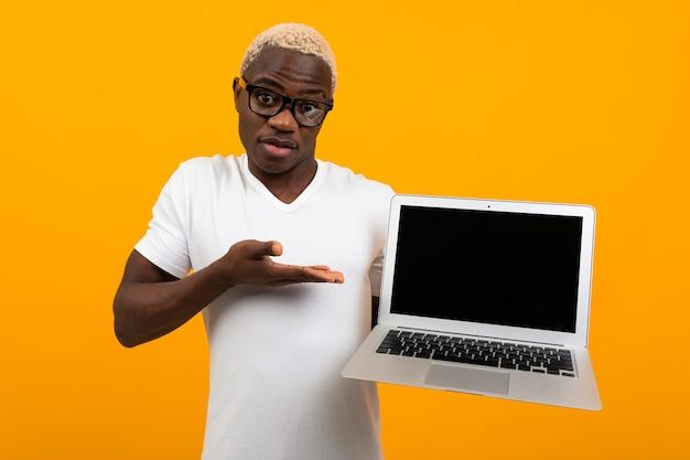 Biznesmena afrykański mężczyzna w szkłach i białej koszulce trzyma laptop z mockup i koloru żółtego odosobnionym tłem