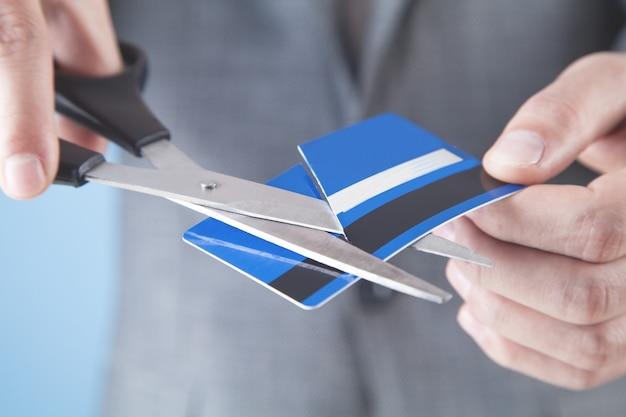 Biznesmena cięcia karty kredytowej nożyczkami biznes