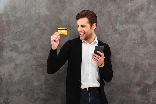 Biznesmena gawędzenie telefonem komórkowym trzyma kredytową kartę.