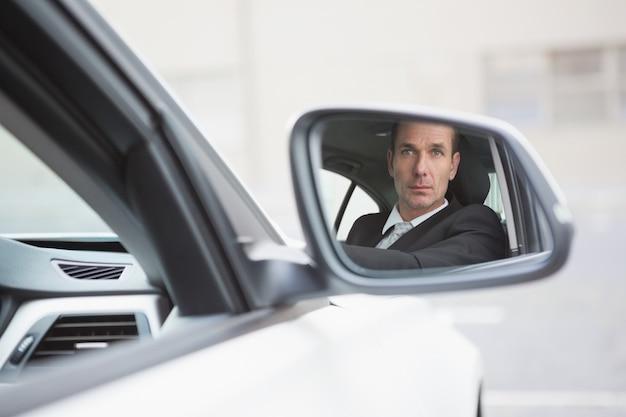 Biznesmena jeżdżenie z jego odbiciem w tylni widoku lustrze