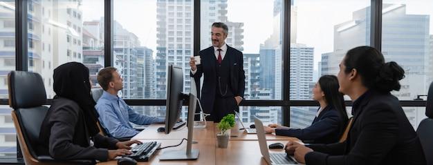 Biznesmena kierownik wyższego szczebla opowiada polisę firma z biznes drużyną podczas gdy pracujący przy biurem