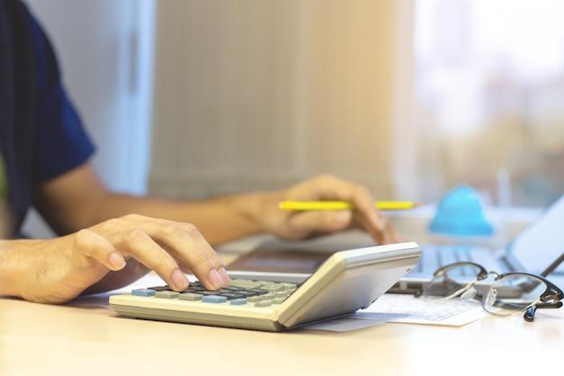 Biznesmena księgowy używa kalkulatora i laptop dla kalkulować finanse przy biurem.