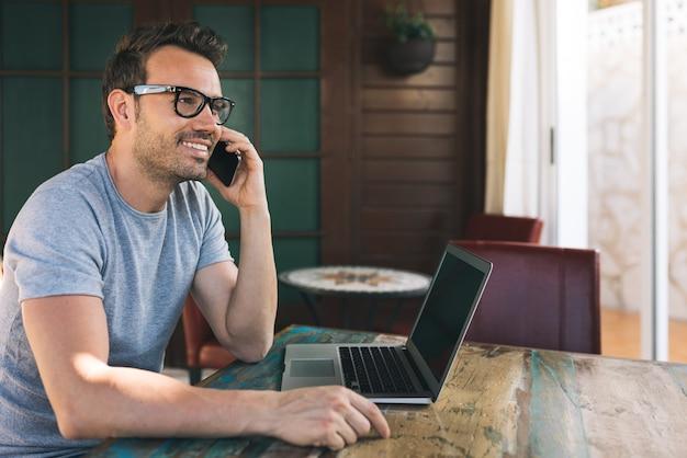 Biznesmena mężczyzna pracuje od domu na telefonie komórkowym