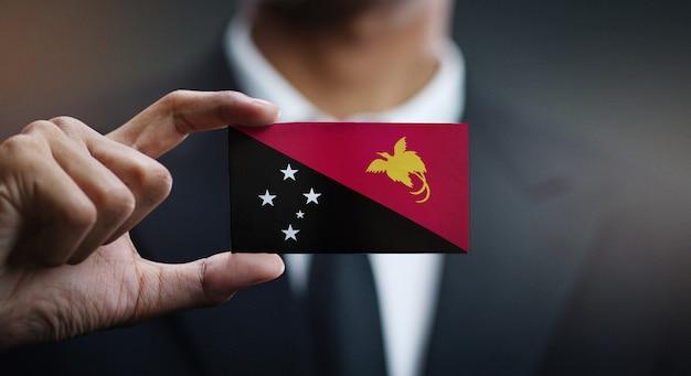 Biznesmena mienia karty papua - nowa gwinei flaga