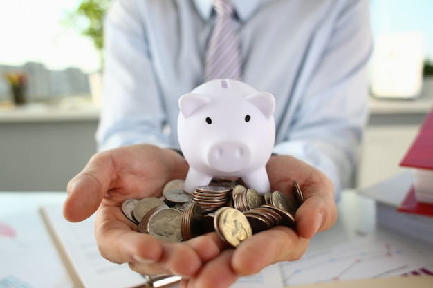 Biznesmena mienia monety i prosiątko bank