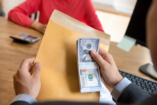 Biznesmena mienia pieniądze za kopertą przy biurem